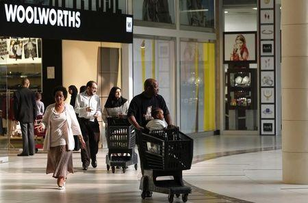 Shoppers leave a Woolworths store at a shopping centre in Lenasia, south of Johannesburg