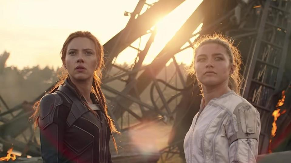 Natasha Romanoff and Yelena Belova stand before fiery wreckage in a moment from Black Widow.