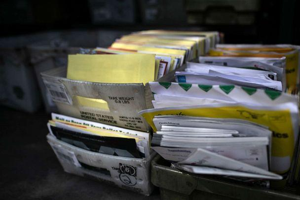 PHOTO: Yellow mail-in ballots and assorted mail sit in a U.S Postal Service truck while being delivered to a residential neighborhood, Oct. 8, 2020, in Phoenix. (John Moore/Getty Images)