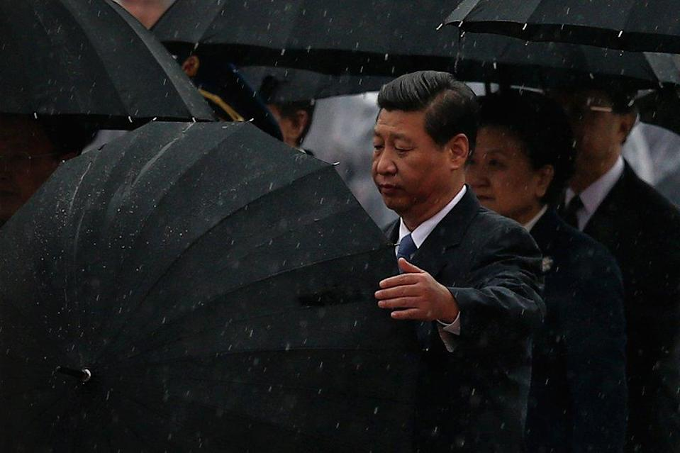 Chinese President Xi Jinping (Left) opens his umbrella, 2013