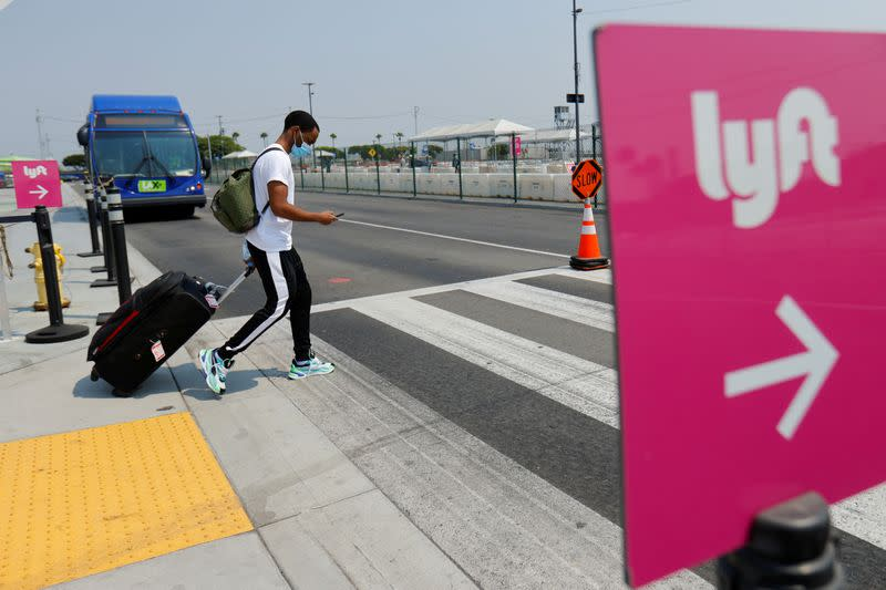 FILE PHOTO: Traveler arrives as Uber and Lyft drivers demonstrate over basic employee rights in California