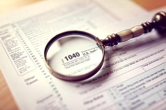 Tax forms with a magnifying glass on top of them on a table.