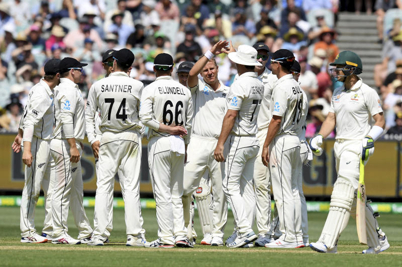 New Zealand players celebrate the wicket of Australia's Tim Paine, right, during play in their cricket test match in Melbourne, Australia, Friday, Dec. 27, 2019. (AP Photo/Andy Brownbill)