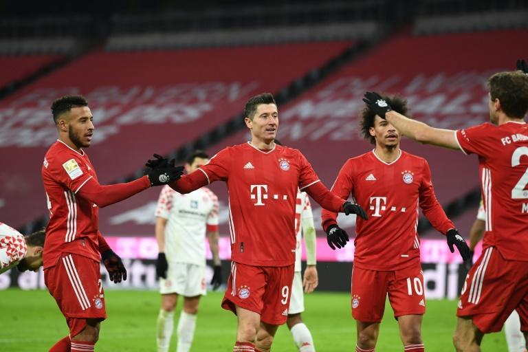 Robert Lewandowski celebrates converting a penalty in Bayern Munich's 5-2 home win against Mainz on Sunday