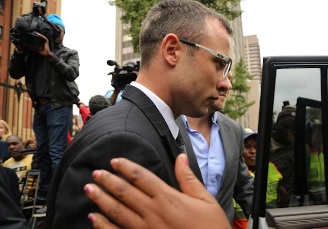 Oscar Pistorius, with unidentified relative leaves the high court in Pretoria, South Africa, Thursday, April 17, 2014. One of Oscar Pistorius' defense experts was grilled by the chief prosecutor for the second day at the Olympic runner's murder trial Thursday, with forensic specialist Roger Dixon's expertise and professionalism in conducting various tests regarding Reeva Steenkamp's shooting death again sternly questioned. Pistorius is charged with premeditated murder for shooting Steenkamp multiple times on Feb. 14, 2013. Prosecutors say that he killed Steenkamp after a fight. The trial was adjourned until May 5. (AP Photo/Themba Hadebe)