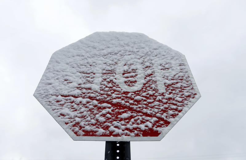 A stop sign is covered in snow in Detroit, Tuesday, April 15, 2014. A spring storm left roads slippery across Michigan and shattered seasonal snowfall records in Detroit and Flint. (AP Photo/Paul Sancya)