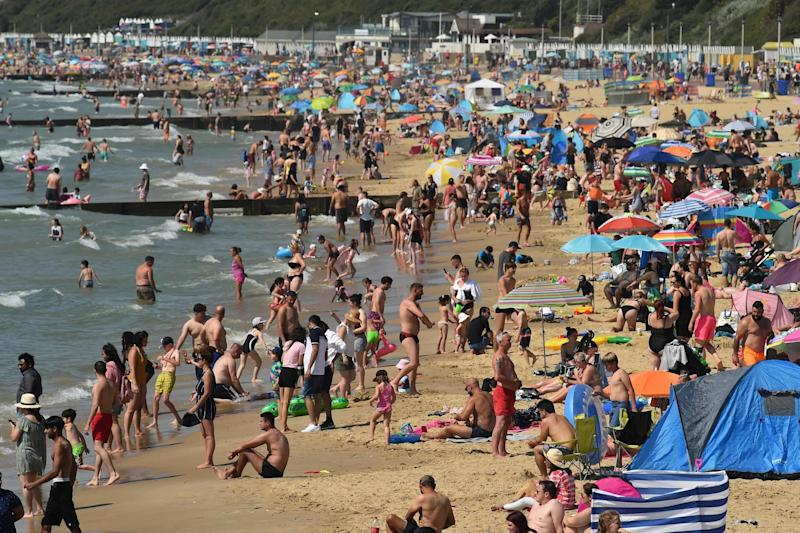 Beachgoers enjoy the sunshine as they sunbathe and play in the sea on Bournemouth beach in Bournemouth, southern England on July 31, 2020: AFP via Getty Images