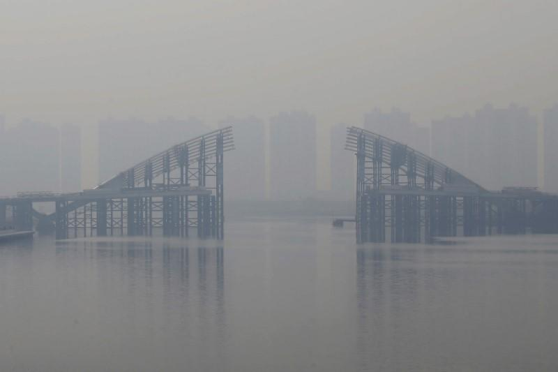 Buildings are seen through smog behind an unfinished bridge near the Yujiapu financial centre