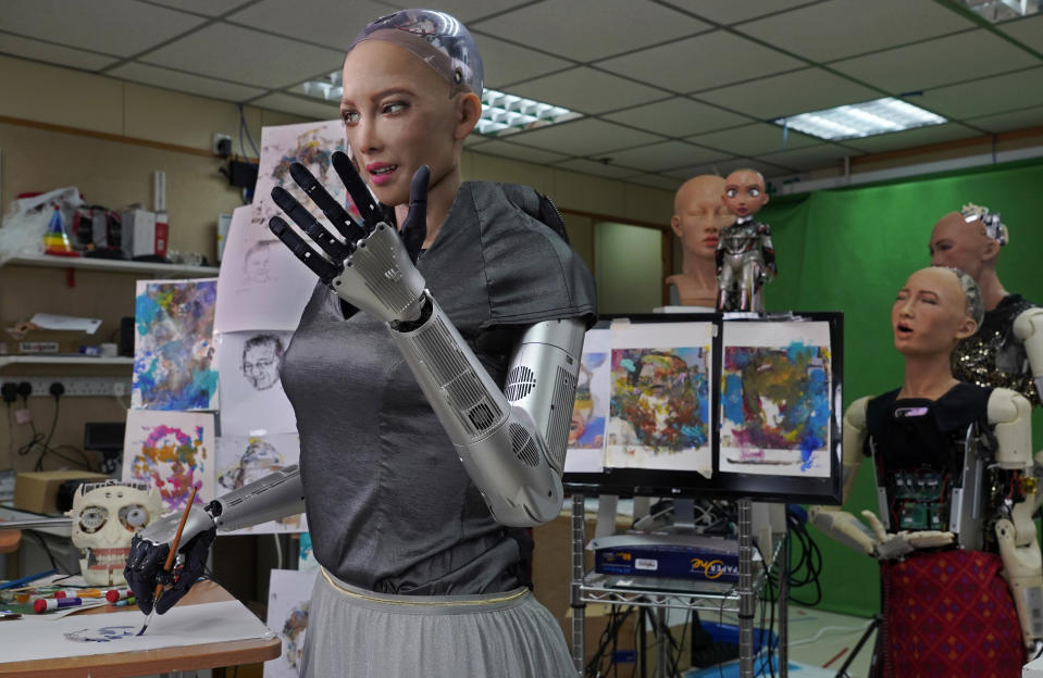 Sophia uses a brush to paint at Hanson Robotics studio in Hong Kong on March 29, 2021. Sophia is a robot of many talents — she speaks, jokes, sings and even makes art. In March, she caused a stir in the art world when a digital work she created as part of a collaboration was sold at an auction for $688,888 in the form of a non-fungible token (NFT). (AP Photo/Vincent Yu)