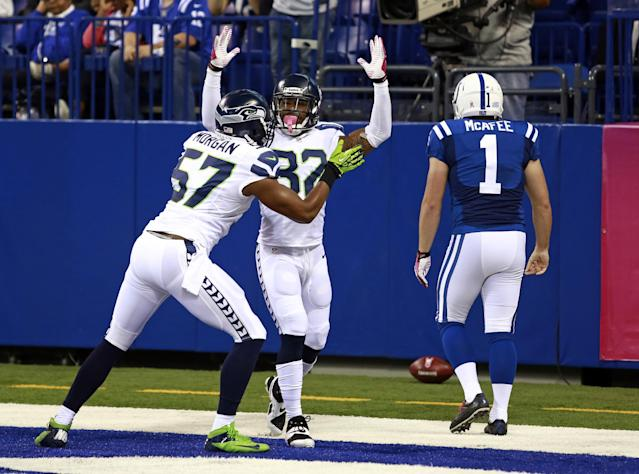 Seattle Seahawks outside linebacker Mike Morgan, left, and strong safety Jeron Johnson celebrates a safety in front of Indianapolis Colts punter Pat McAfee during the first half of an NFL football game in Indianapolis, Sunday, Oct. 6, 2013. (AP Photo/Brent R. Smith)