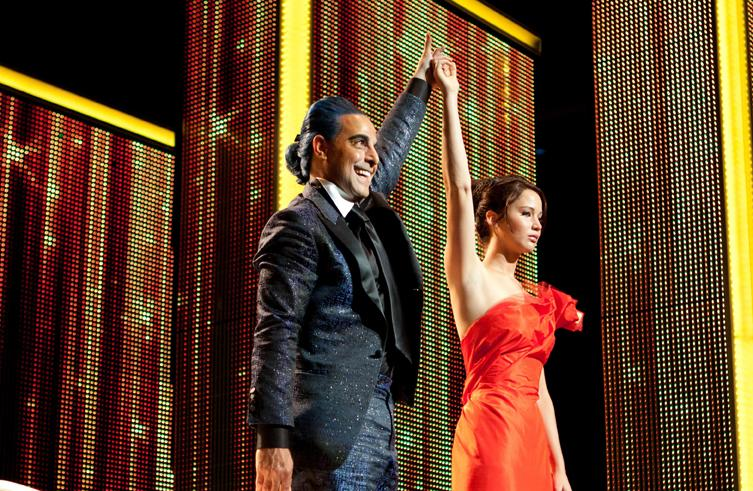 Hunger Games host Caesar Flickerman (Stanley Tucci) introduces newly-styled tribute Katniss Everdeen (Jennifer Lawrence) to the nation of Panem.