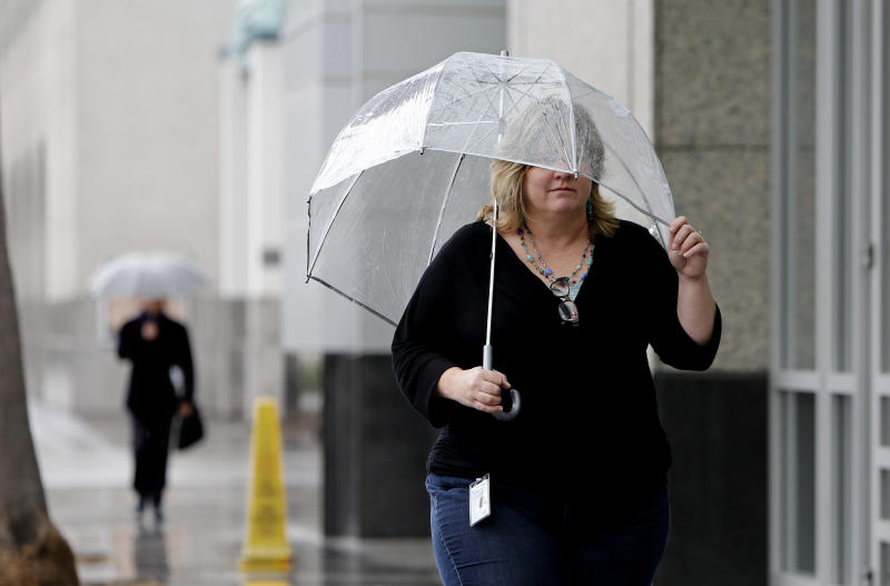 Molly Emslie found the need for an umbrella as showers swept through Sacramento, Calif., Friday, Feb. 7, 2014. Drought-stricken California is getting some relief as a storm system the likes of which, forecasters say, the region has not seen in more than a year.(AP Photo/Rich Pedroncelli)
