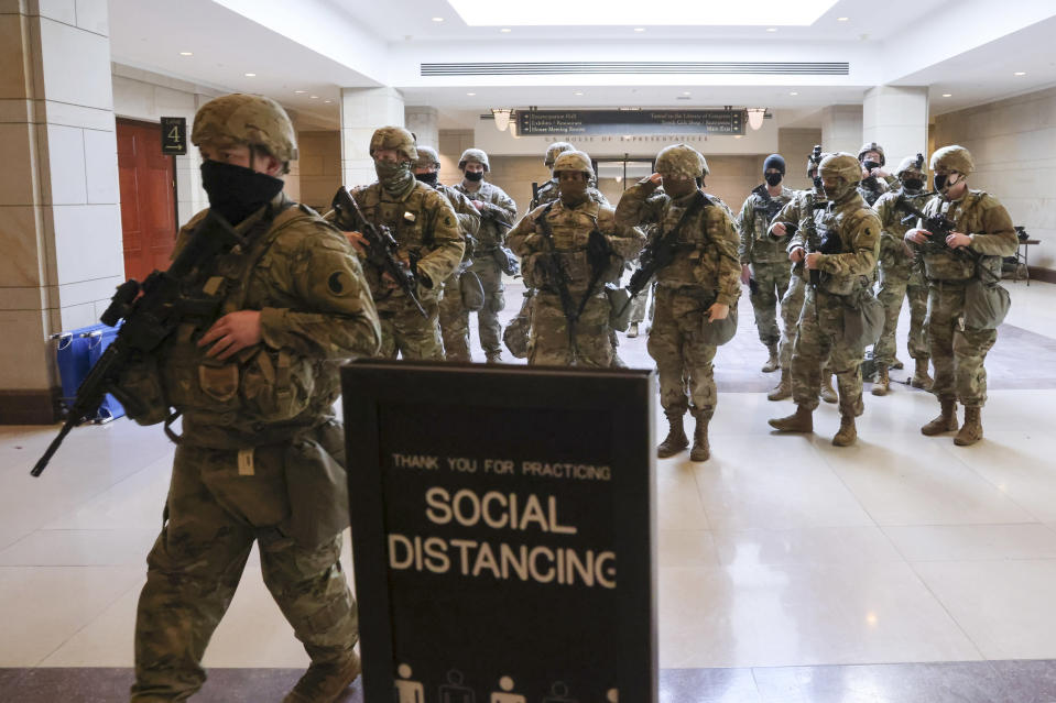 National Guard troops walk in the U.S. Capitol Visitor Center during a rehearsal for President-elect Joe Biden's inauguration ceremony, at the Capitol in Washington, Monday, Jan. 18, 2021. (Jonathan Ernst/Pool via AP)