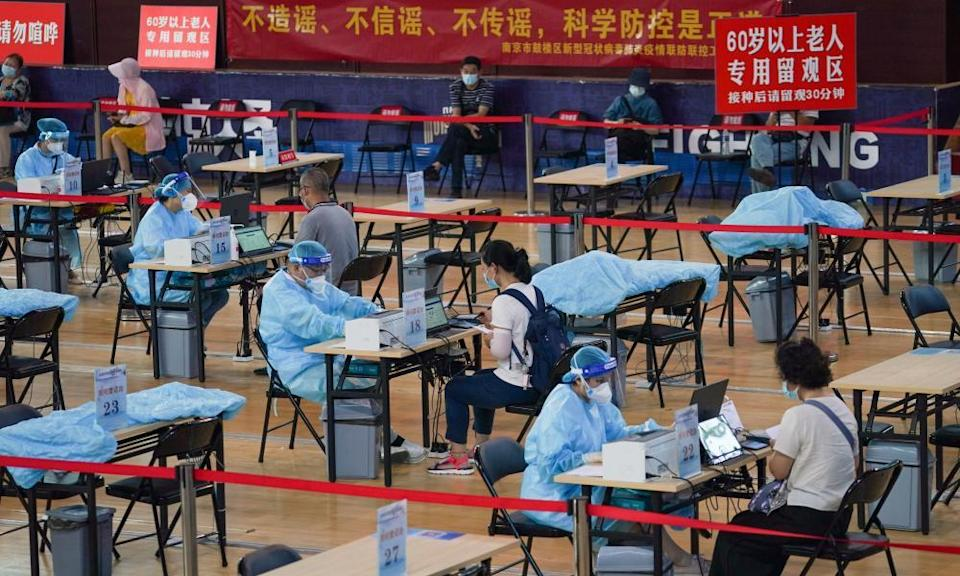 Residents register before getting inoculated against the COVID-19 virus at a vaccination site in a stadium in Nanjing, capital of east China's Jiangsu Province
