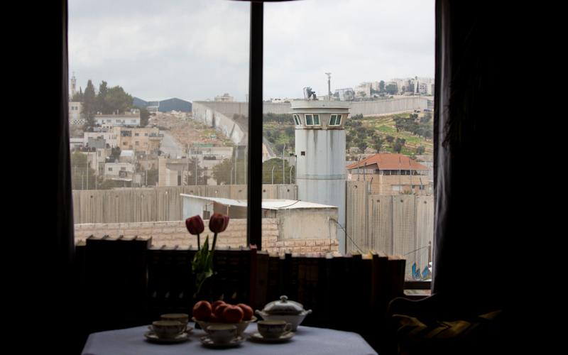An Israeli security watch tower is seen from one of the rooms - Credit: AP