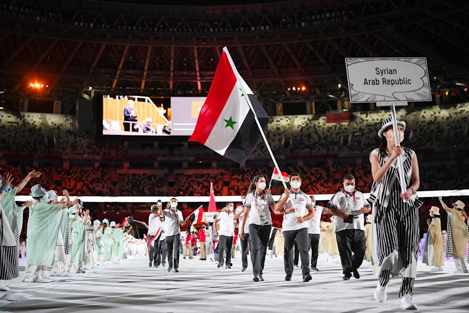 <p>TOKYO, JAPAN - JULY 23: Flag bearers Hend Zaza and Ahmad Saber Hamcho of Team Syria during the Opening Ceremony of the Tokyo 2020 Olympic Games at Olympic Stadium on July 23, 2021 in Tokyo, Japan. (Photo by Matthias Hangst/Getty Images)</p>