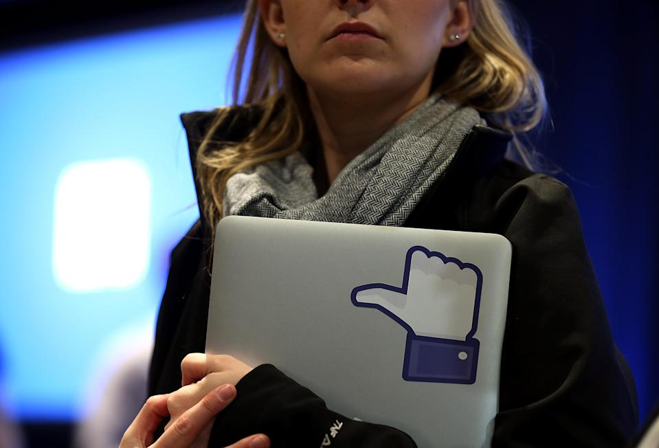 """A Facebook employee holds a laptop with a """"like"""" sticker on it during an event at Facebook headquarters during an event at Facebook headquarters on April 4, 2013 in Menlo Park, California. (Photo by Justin Sullivan/Getty Images)"""