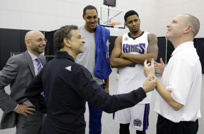Vivek Ranadive (second from left) shares his ideas with with Kings coach Michael Malone. (AP/Rich Pedroncelli)
