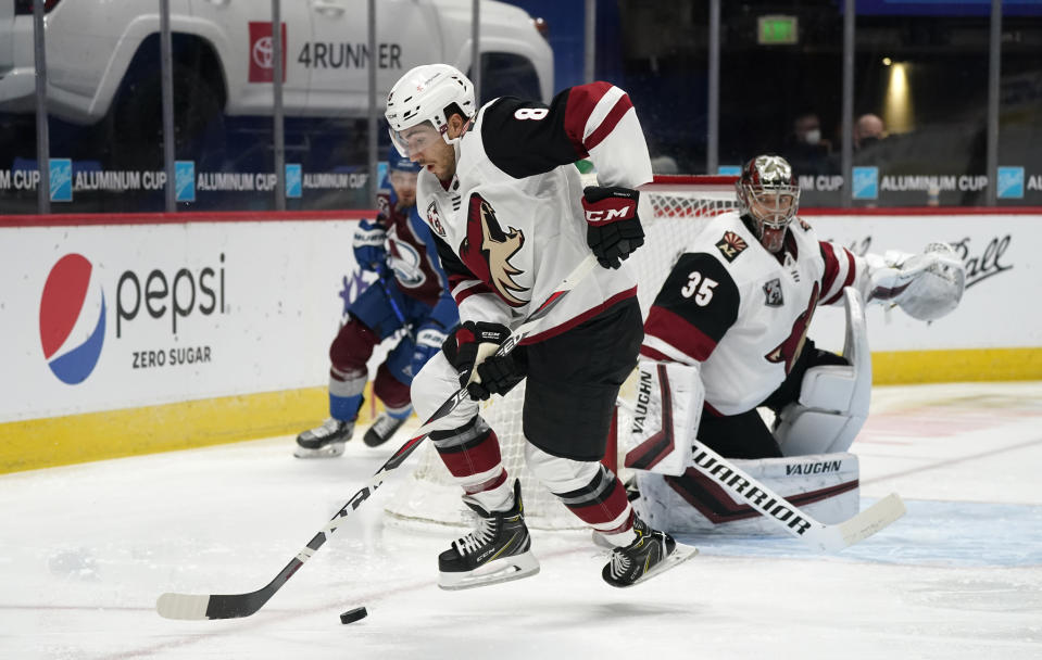 Arizona Coyotes center Nick Schmaltz, front, picks up the puck in front of Coyotes goaltender Darcy Kuemper as Colorado Avalanche right wing Valeri Nichushkin, back, trails the play in the first period of an NHL hockey game Monday, March 8, 2021, in downtown Denver. (AP Photo/David Zalubowski)