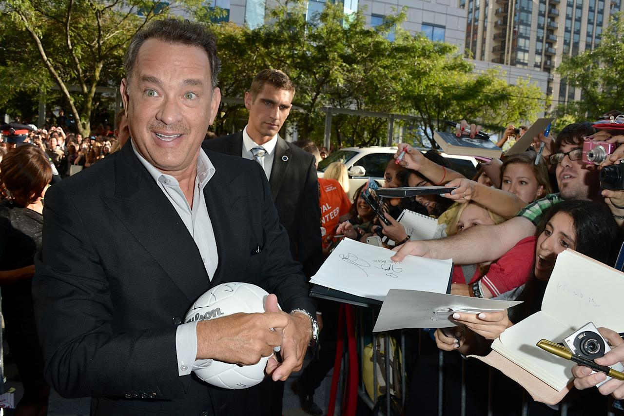 "Tom Hanks is over the moon to sign a Wilson volleyball at the ""Cloud Atlas"" premiere."