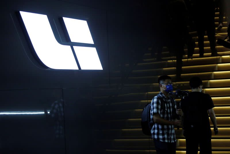 People stand near the logo of Chinese EV maker Li Auto at a product launch event in Beijing