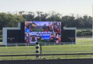 """A message reading, """"Thanks Arlington for a Million Memories"""" plays on the infield video screen at Arlington Park in Arlington Heights, Ill., between races on Saturday, Sept. 18, 2021. The racetrack is expected to close after the completion of racing on Sept. 25, with ownership taking bids for the future of the land. (AP Photo/Steve Whyno)"""