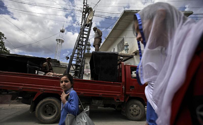 In this Monday, April 30, 2012 photo, Pakistani schoolgirls walk by municipality workers fixing electrical wires in Abbottabad, Pakistan. One year since U.S. commandos flew into this army town and killed Osama bin Laden, Pakistan has tried to close one of the most notorious chapters in its history. The compound that housed him for six years was razed to the ground, and the wives and children who shared the hideaway were flown to Saudi Arabia just last week. (AP Photo/Muhammed Muheisen)