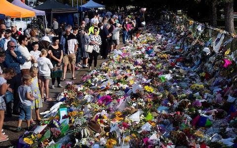 <span>Floral tributes to those who were gunned down at the two mosques are seen against a wall bordering the Botanical Garden in Christchurch</span> <span>Credit: MARTY MELVILLE/AFP </span>