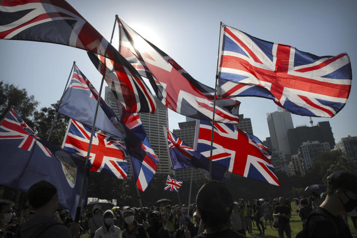 Demonstrators wave British flags during an anti-government protest in Hong Kong, Saturday, Nov. 2, 2019. Defying a police ban, thousands of black-clad masked protesters are streaming into Hong Kong's central shopping district for another rally demanding autonomy in the Chinese territory as Beijing indicated it could tighten its grip. (AP Photo/Kin Cheung)