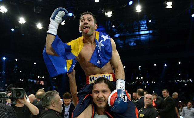Challenger Felix Sturm from Germany celebrates his victory after his middleweight title bout against IBC World Champion Darren Barker of Britain in Stuttgart, southern Germany, Saturday, Dec. 7, 2013. (AP Photo/Daniel Kopatsch)