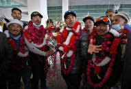 Nepalese climber Nirmal Purja, center, and his team, who recently made history by scaling the K2 summit in the winter season, are greeted by local tour operators upon their arrival at airport in Islamabad, Pakistan, Thursday, Jan. 21, 2021. Winter winds on K2 can blow at more than 200 km per hour (125 miles per hour) and temperatures can drop to minus 60 C (minus 76 F), an official of Pakistan's Alpine Club, Karrar Haideri said. (AP Photo/Anjum Naveed)
