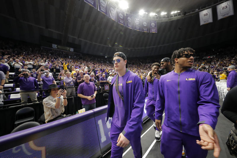 LSU quarterback Joe Burrow, lert, and wide receiver Ja'Marr Chase walk into the Pete Maravich Assembly center during a celebration for their NCAA college football championship, Saturday, Jan. 18, 2020, on the LSU campus in Baton Rouge, La. (AP Photo/Gerald Herbert)