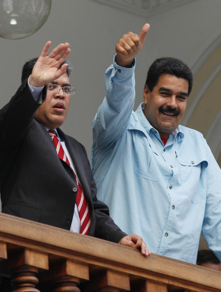 """Venezuela's President Nicolas Maduro, right, and Foreign Minister Elias Jaua, acknowledge well-wishers from the balcony of the Foreign Ministry after meeting with South Africa's foreign minister, in Caracas, Venezuela, Thursday, Sept. 19, 2013. Jaua said Thursday that the United States has prohibited a planned flight by Maduro from passing through U.S. airspace over Puerto Rico. The foreign minister said that the flight had been scheduled to pass over the U.S. territory on Friday on its way to China. He characterized the U.S. action as an """"aggression."""" (AP Photo/Ariana Cubillos)"""