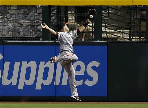 San Francisco Giants' Juan Perez makes a leaping catch on a fly ball hit by Arizona Diamondbacks' Paul Goldschmidt during the first inning in a baseball game on Sunday, June 9, 2013, in Phoenix. (AP Photo/Ross D. Franklin)