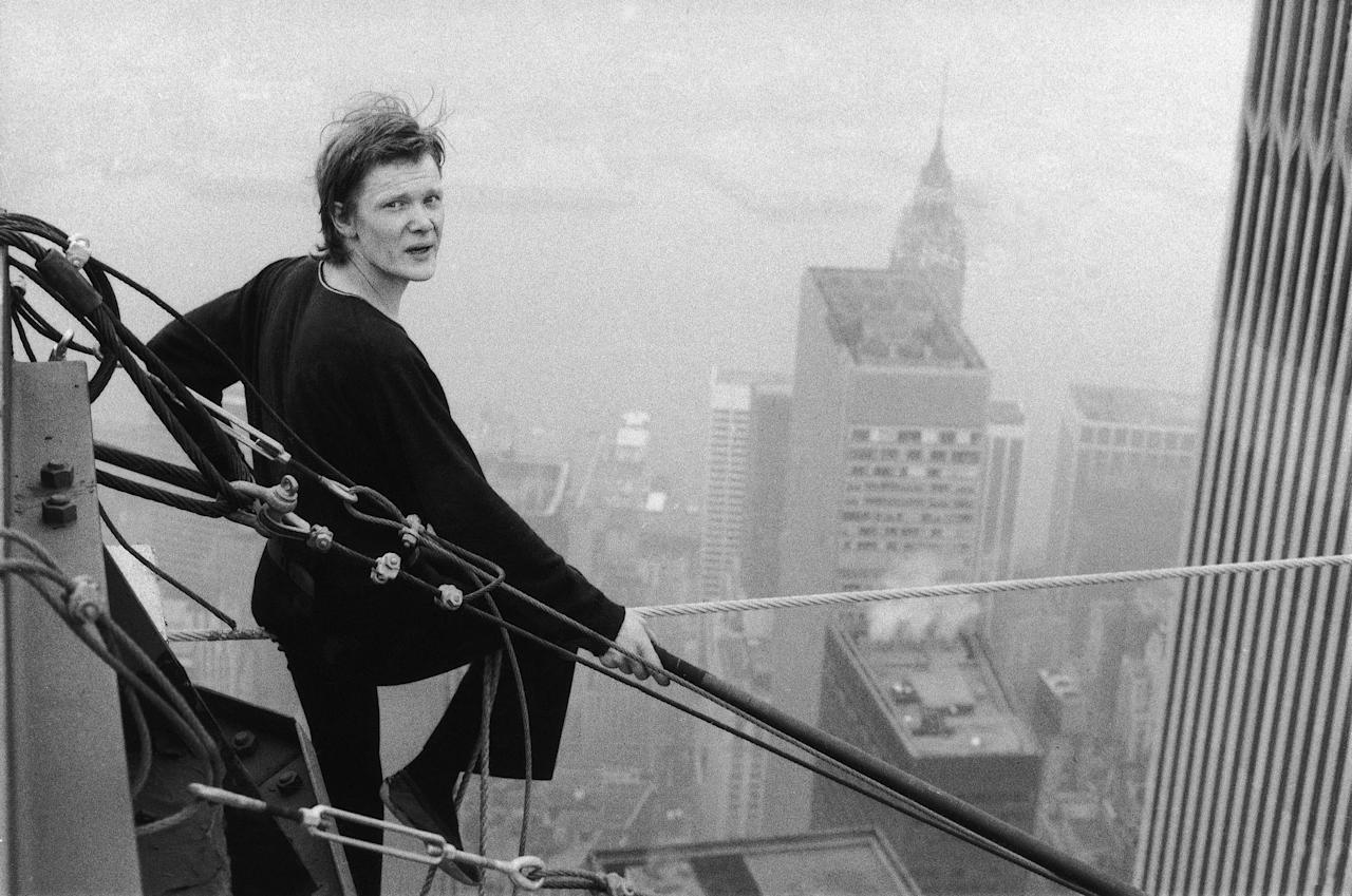 French tightrope walker Philippe Petit, 24, looks back at the  photographer as he rests between walks across a cable stretched between  New York's World Trade Center towers high above the city on Wednesday,  August 7, 1974. Petit crossed the cable twice and at one point, hung by  his heels. The Frenchman and two assistants apparently hid in one of the  towers and set the cable up before dawn, police said. (AP Photo/Alan  Welner)