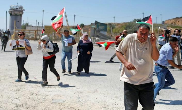 Palestinian demonstrators react to stun grenades during a protest in solidarity with prisoners held in Israeli jails near Ofer Prison in the occupied West Bank on Thursday (AFP Photo/ABBAS MOMANI)