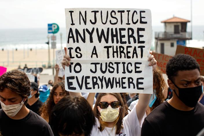 """<i>A woman holds up a sign with the Martin Luther King Jr. quote """"Injustice anywhere is a threat to justice everywhere"""" during a protest in Manhattan Beach, California, on June 2.</i>"""