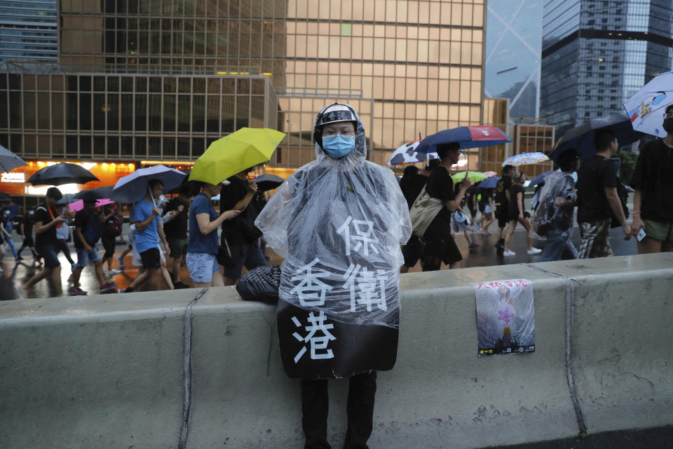 """A protester in rain coat wears a sign which reads """"Protect Hong Kong"""" during a march in Hong Kong on Sunday, Aug. 18, 2019. Heavy rain fell on tens of thousands of umbrella-toting protesters Sunday as they marched from a packed park and filled a major road in Hong Kong, where mass pro-democracy demonstrations have become a regular weekend activity over the summer. (AP Photo/Kin Cheung)"""