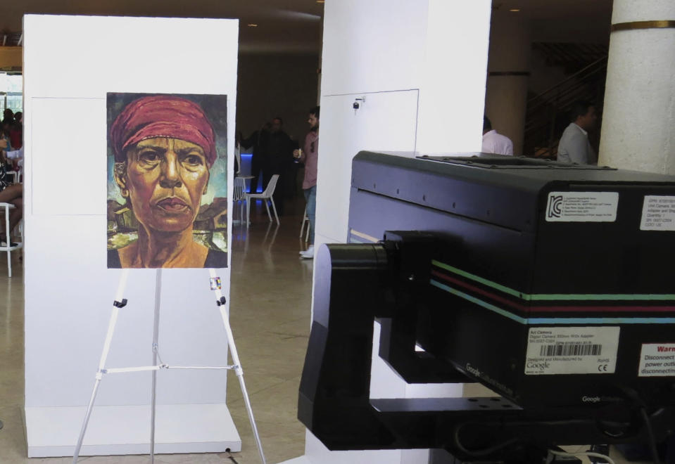 """CORRECTS TO REMOVE PORTRAYALS OF WORKING CLASS WOMEN IN FIRST SENTENCE - A depiction of """"Goyita,"""" a 1953 painting by Rafael Tufiño Figueroa of his mother that broke from conventional portraits of the time, is placed in front of Google's Art Camera in San Juan Puerto Rico, Thursday, Nov. 7, 2019. (AP Photo/Dánica Coto)"""