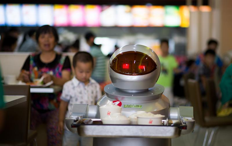 A robot carries food to customers in a restaurant in Kunshan, China on August 13, 2014 (AFP Photo/Johannes Eisele)