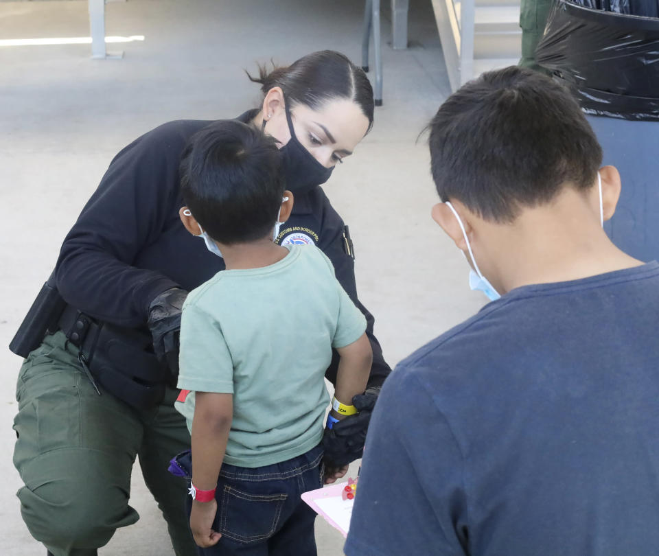 This May 4, 2021, photo provided by The U.S. Border Patrol shows a U.S. Border Patrol Processing Coordinator places a color-coded arm band on an underaged child at the Central Processing Center in El Paso, Texas. The Border Patrol says agents spend about 40% of their time on custody care and administrative tasks that are unrelated to border security, creating a staffing challenge. (U.S. Border Patrol via AP)