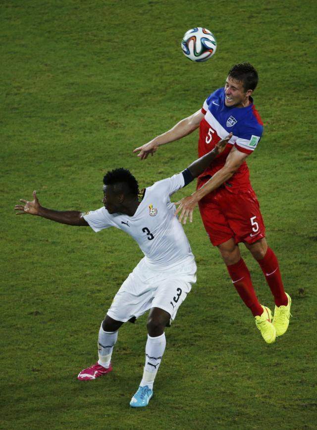 Ghana's Asamoah Gyan (L) fights for the ball with Matt Besler of the U.S. during their 2014 World Cup Group G soccer match at the Dunas arena in Natal June 16, 2014. REUTERS/Carlos Barria (BRAZIL - Tags: SOCCER SPORT WORLD CUP)