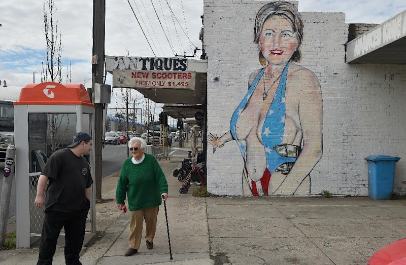 People walk past a mural of US presidential nominee Hillary Clinton clad in a swimsuit, created by street artist Lushsux, in West Footscray, Melbourne on July 30, 2016