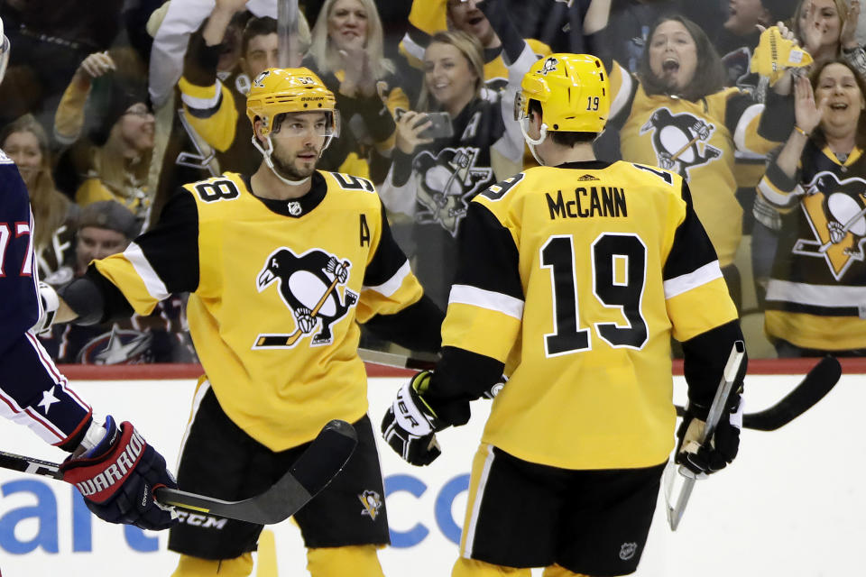 Pittsburgh Penguins' Kris Letang (58) celebrates his goal with Jared McCann during the second period of an NHL hockey game against the Columbus Blue Jackets in Pittsburgh, Saturday, Oct. 5, 2019. (AP Photo/Gene J. Puskar)