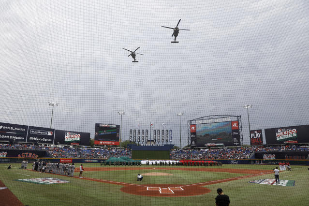 Helicopters fly over the stadium at the start of a baseball game between the Los Angeles Angels and Houston Astros, in Monterrey, Mexico, Sunday, May 5, 2019. (AP Photo/Rebecca Blackwell)