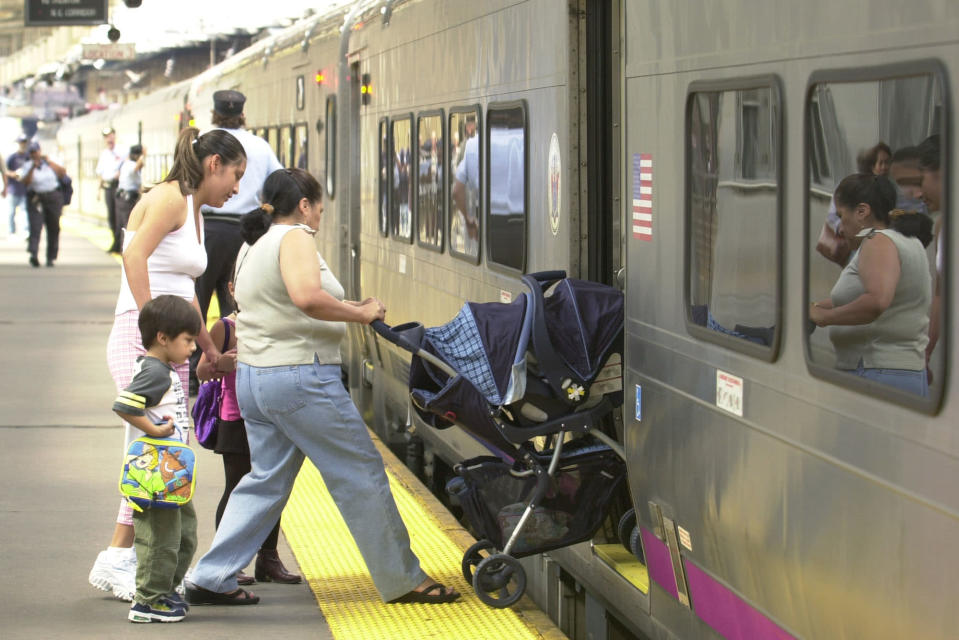 A woman wheels a baby stroller onto a New Jersey Transit train at Penn Station in Newark, N.J., Thursday, July 15, 2004. (AP Photo/Mike Derer)