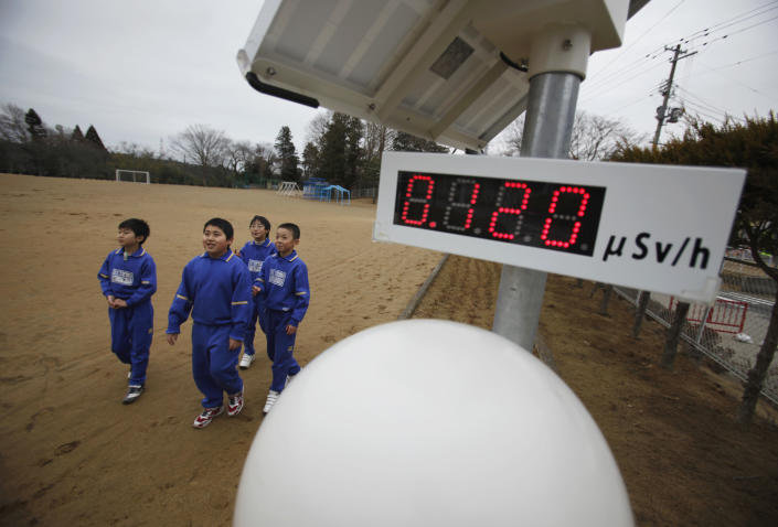 Students walk near a geiger counter, measuring a radiation level of 0.12 microsievert per hour, at Omika Elementary School, located about 21 km (13 miles) from the tsunami-crippled Fukushima Daiichi nuclear power plant, in Minamisoma, Fukushima prefecture, March 8, 2012, ahead of the one-year anniversary of the March 11 earthquake and tsunami. The reopened elementary school, which is the nearest one located to the crippled nuclear power plant, had 205 students before the March 11, 2011 disasters. However, only 91 students remained following its reopening on October 17, 2011. REUTERS/Toru Hanai (JAPAN - Tags: DISASTER ANNIVERSARY ENVIRONMENT)