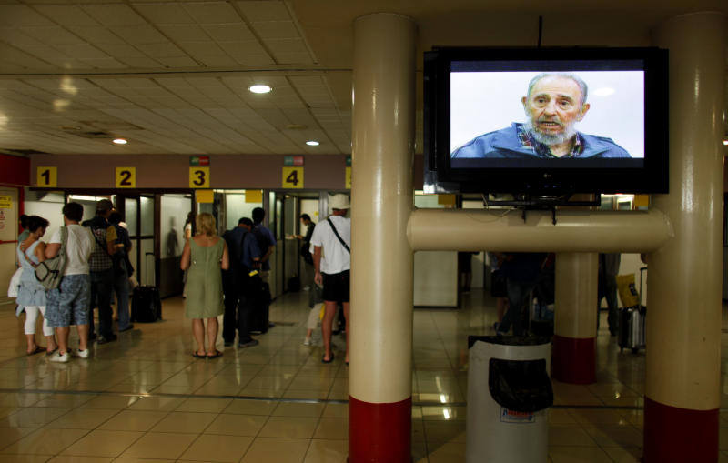 """FILE - In this Monday, July 12, 2010, People line up to check with migration officials before departing at the Jose Marti International airport in Havana, Cuba, next to a screen showing Cuba's leader Fidel Castro during an interview with Cubavision."""" Cuba's government appears on the verge of a momentous decision that could end a half-century of travel restrictions that make it difficult to leave the Communist-run island, even for vacation. (AP Photo/Javier Galeano, File)"""