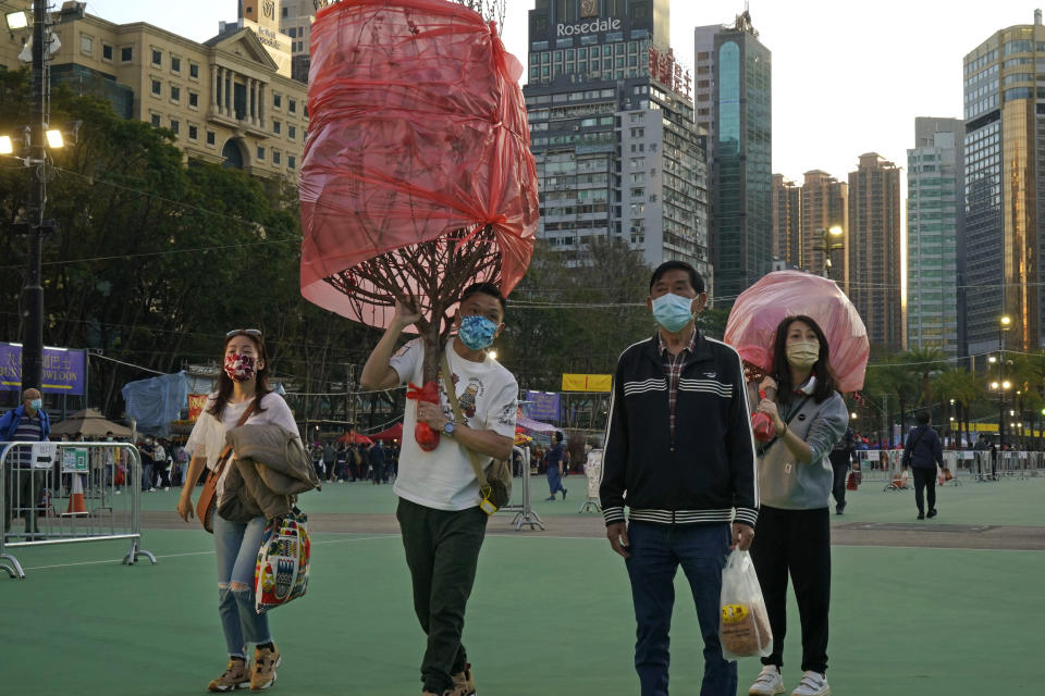 Customers wearing face masks to protect against the spread of the coronavirus, carry peach blossom trees at the flower markets in Victoria Park of Hong Kong, Saturday, Feb. 6, 2021. Traditional Lunar New Year flower markets opened Saturday in Hong Kong, after a government virus policy U-turn. At the biggest venue, Victoria Park next to the popular downtown shopping district of Causeway Bay, the eerie emptiness is in stark contrast to the usual bustle of capacity crowds.(AP Photo/Kin Cheung)