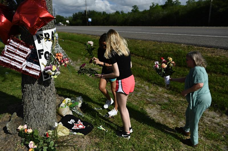 Residents leave flowers at a memorial for victims of a mass shooting at Santa Fe High School in Santa Fe, Texas (AFP Photo/Brendan Smialowski)